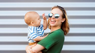 French baby names: Stylish young mom holds baby wearing striped shirt