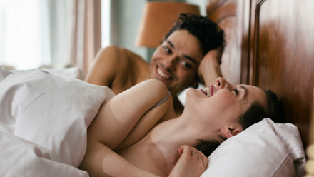 Couple in bed laughing