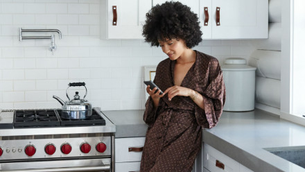 Woman in a robe looking at her phone