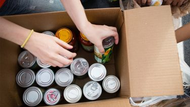 Hands putting canned foods in a cardboard box
