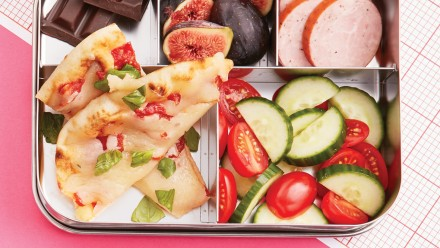 bento box with pizza, fig, chocolate, veggies and fruit