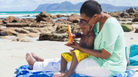 Woman sitting on the beach with child on lap, applying sunscreen