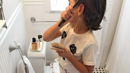 Kid brushing their hair in front of the bathroom mirror