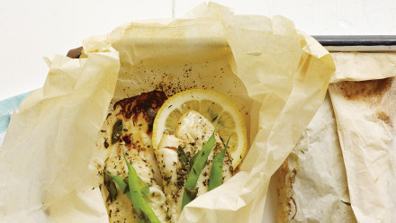 White fish in parchment paper package with lemons and green beans
