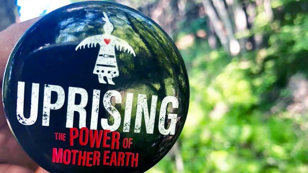 Person holding up a button that reads Uprising the Power of Mother Earth in front of a garden