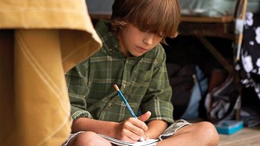 kid writing a letter home while at camp