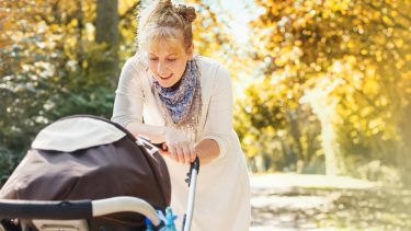 woman looking at her baby in a stroller while on a walk