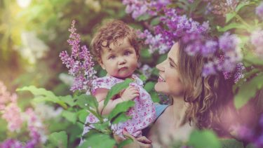 Mom holding baby girl while surrounded by purple flowers