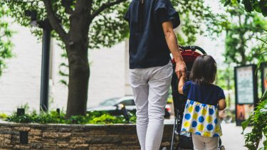 Mom pushing stroller while holding hands with young daughter outside
