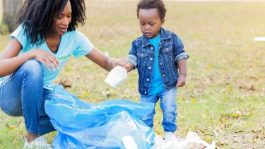 Mother with kid recycling and picking up trash in the grass