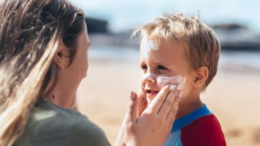Mom putting sunscreen on her child's face