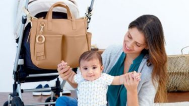 mom playing with baby with stroller and diaper bag behind them
