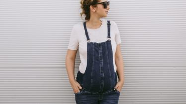 Second trimester: Fashionable pregnant woman in overalls