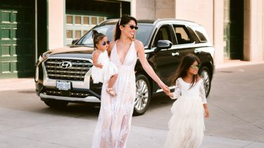Trisha Enriquez and her daughters in white dresses posed in front of the Hyundai Palisade