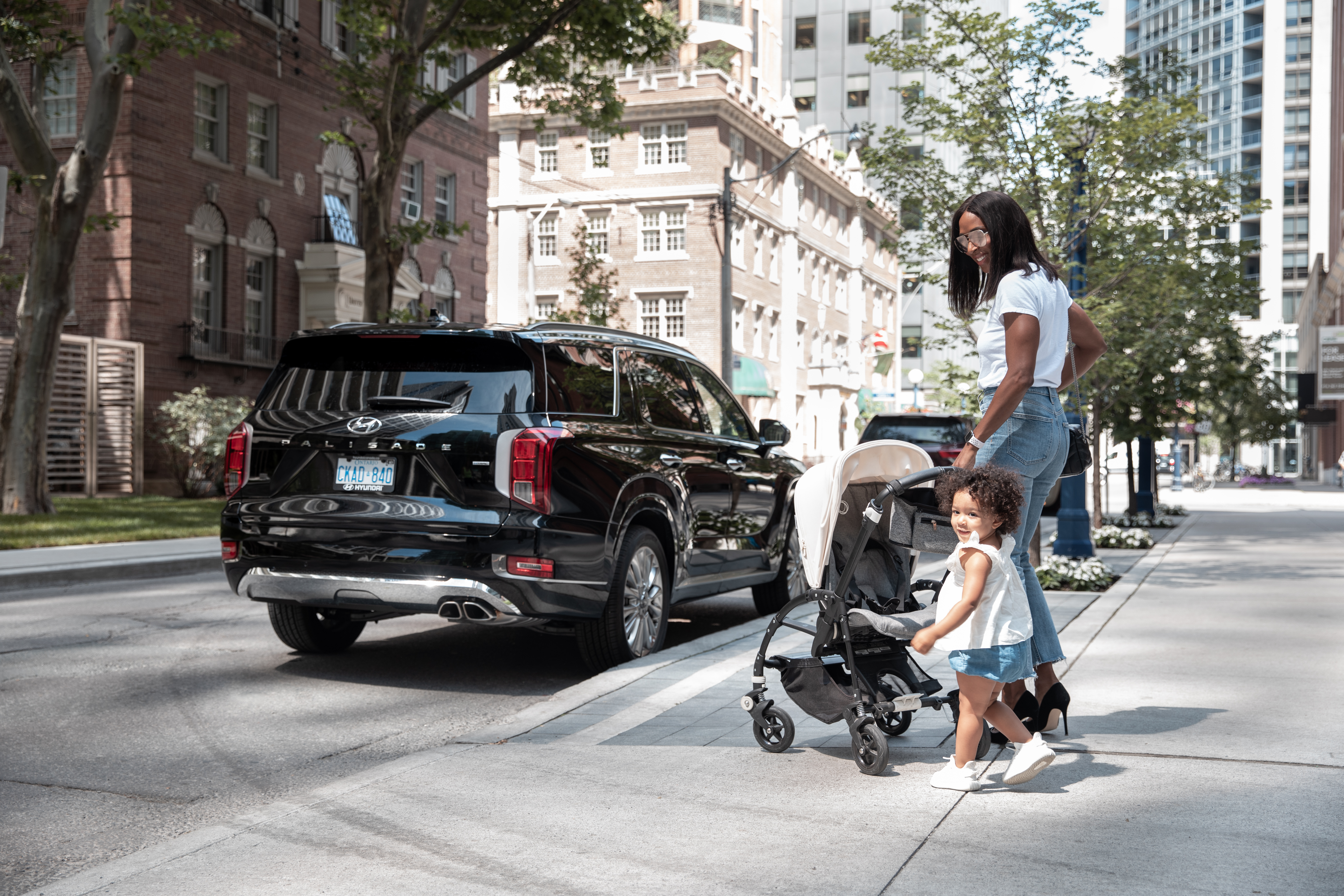Woman and toddler with stroller walking up to the Hyundai Palisade