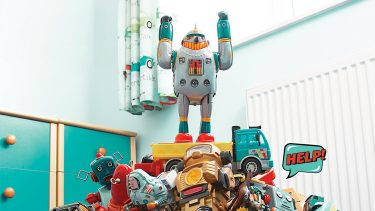Toy robot standing on a pile of toys with his arms raised.