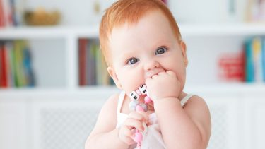 Teething rash: Infant chewing on her first