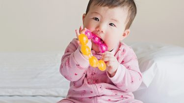baby chewing on a teething ring