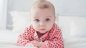 Creative baby names: A cute baby in a polka-dot pink jumper looks at the camera