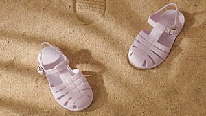 a photo of lavender jelly sandals for kids in the sand