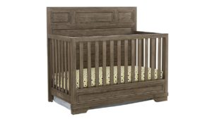 The Westwood Design Foundry Convertible Crib, a brown wooden baby crib with spotted sheets