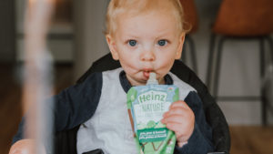 Close-up of baby holding and eating from a Heinz By Nature pouch