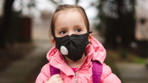 Young kid wearing a face mask with a valve