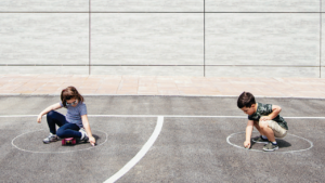two young children doing chalk drawings