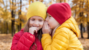two kids outside on a fall day whispering secrets to each other
