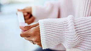 A woman's arms in a pink ribbed sweater holding a pregnancy test
