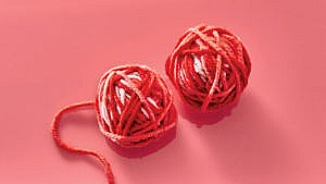 Photo of two small balls of yarn in red and pink tones
