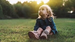 a little girl sits in a field looking towards the sky deep in thought for a story on body image issues in little kids
