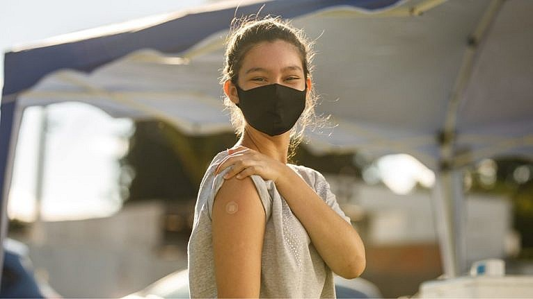 young girl triumphantly showing her arm with a small bandaid covering her vaccine spot