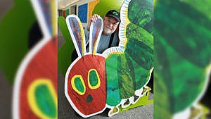 Author and illustrator Eric Carle poses with a large caterpillar cardboard cutout