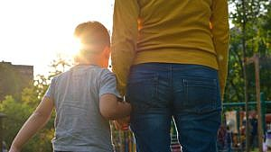 an image showing the backs of a mom and child holding hands standing in front of a playground