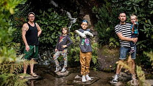 Photo of a family posing by waterfall surrounded by lush flora