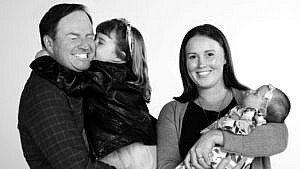 black and white photo of Steve Patterson with his wife and two kids