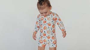 baby wearing a white sunsuit with peaches