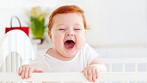 A baby stands in their crib with their mouth open looking gleeful