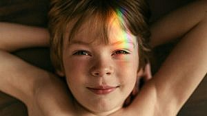 a kid smiling at the camera with a beam of rainbow coloured light across his face
