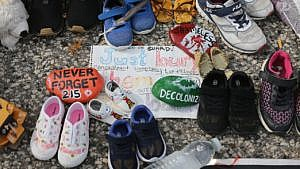 a collection of children's shoes on pavement with rocks and a note in the middle