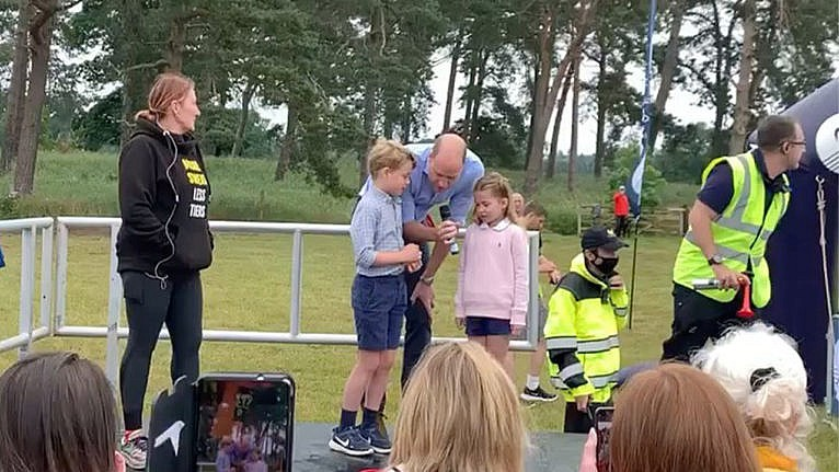still from a clip of Prince William and his two elder kids, Prince George and Princess Charlotte, kicking off a race.