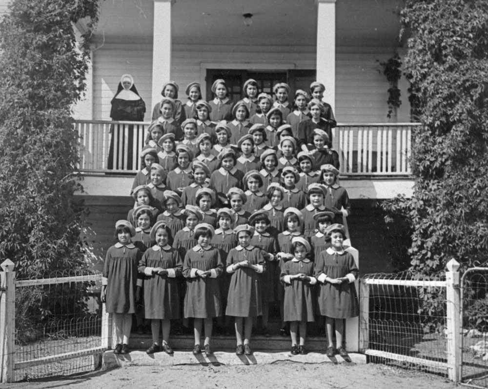 a group of female students and a nun standing outside of a residential school