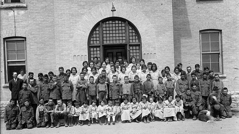 Indigenous children outside of a residential school with staff