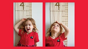 a young child stands in front of a fabric wall ruler to measure her height