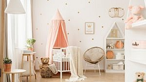 a decorated nursery with a crib, chair, bookshelf and toys