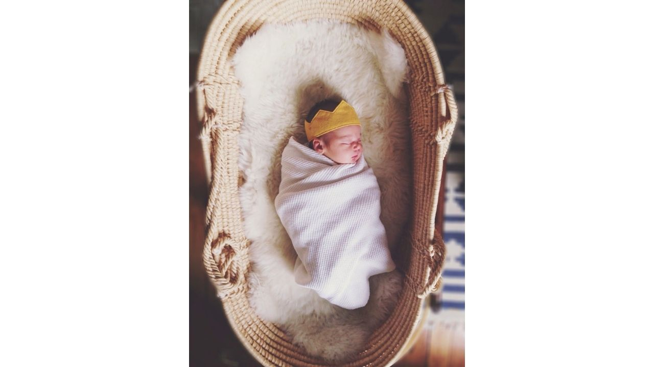 swaddled baby lying in a moses basket