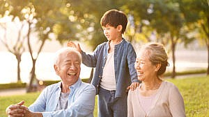 grandparents spending time outside with their grandson