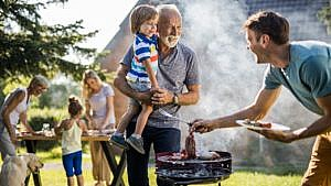a granddad holds his grandchild outside at a family barbecue