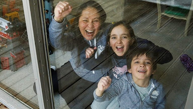 a mom and her two kids through a window